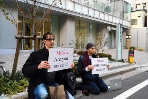 Bitcoin traders Kolin Burges, right, of London and Aaron, an American who gave only his first name, hold protest signs in front of the office tower housing Mt. Gox in Tokyo on Tuesday. (Associated Press)